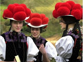 Red bobbles on hats. Girls with red pompom hats.