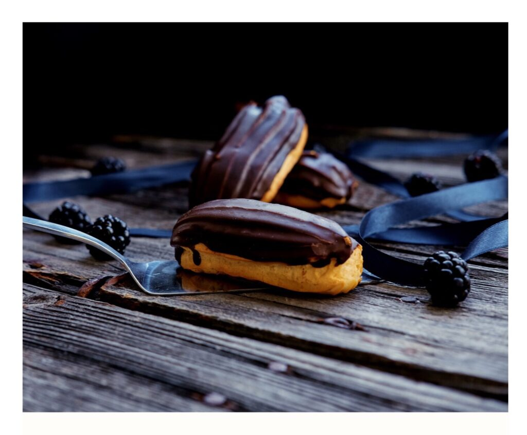 Crisp Choux pastry piped into eclairs. Filled with cream and dipped in a chocolate glaze